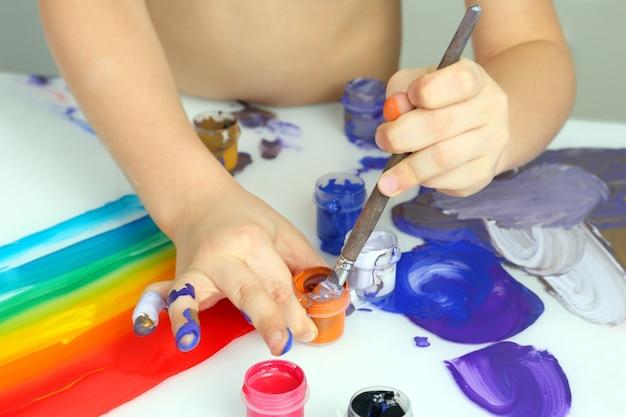 Ręka dziecka rysuje kolory malarskie