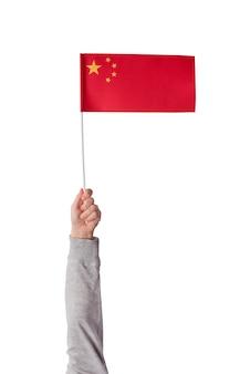 Ręka dziecka trzyma flagę chin na białym tle na białej przestrzeni. czerwona flaga z gwiazdami. rama pionowa