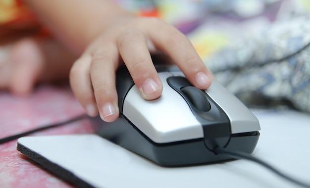 Ręka dziecka trzyma mysz komputerową lub klawiaturę. dziecko uczy się online i gra na komputerze w domu. koncepcja szkoły, edukacji, zabawy i technologii.