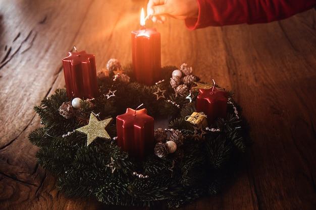 Ręka dziecka zapala pierwszą świeczkę na wieńcu adwentowym zgodnie z tradycją cztery tygodnie przed bożym narodzeniem