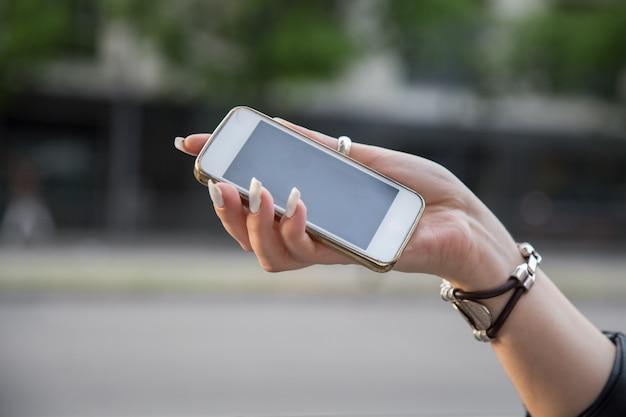 Ręka dziewczyna trzyma mądrze telefon na miasto ulicie