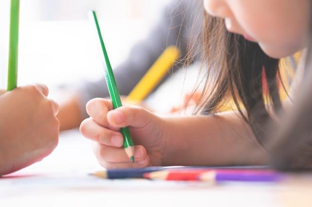 Ręka dziewczyny jest rysunek w klasie sztuki przedszkola