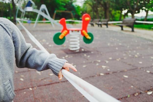 Ręka dziewczyny próbuje wejść na plac zabaw zamknięty przez covid19.