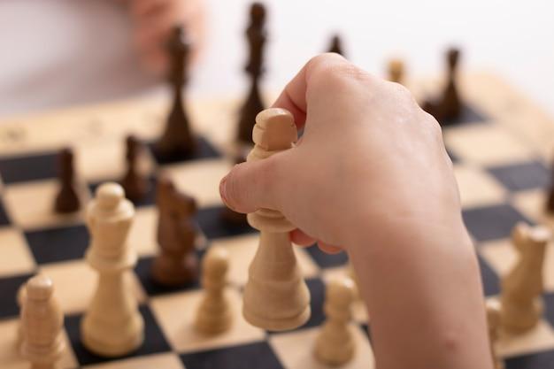 Ręka dziewczyny przesuwająca króla szachów z bliska