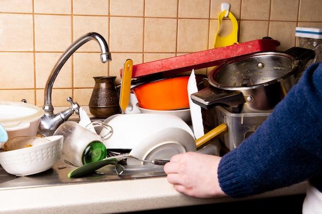 Ręka dziewczyny w pobliżu wielu brudnych naczyń leżących w zlewie w kuchni, które chcesz umyć