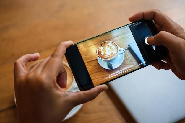 Ręka fotografuje gorącą latte art filiżankę z pianką artystyczną na drewnianym stole