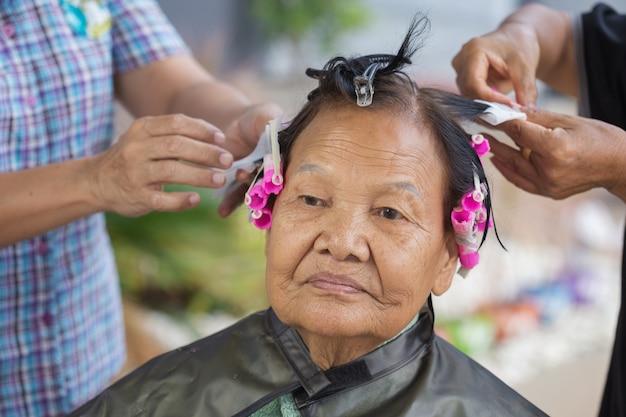 Ręka fryzjerka robi perm toczenia włosów starszy kobieta