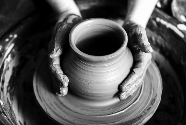 Ręka garncarza robi gliniany garnek na tle