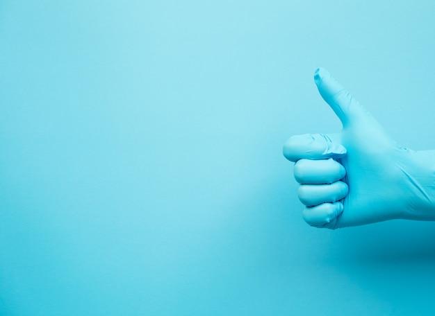 Ręka gest doktorskie jest ubranym błękitne rękawiczki na błękitnym tle, podpisuje dla nie dobrego