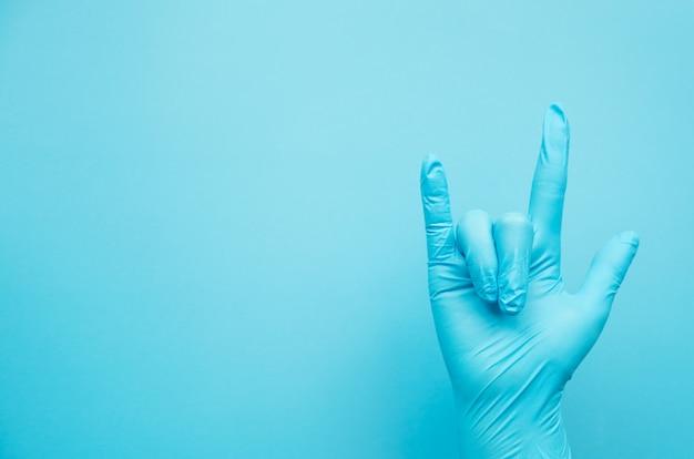Ręka gest doktorskie jest ubranym błękitne rękawiczki na błękitnym tle, znak dla miłości