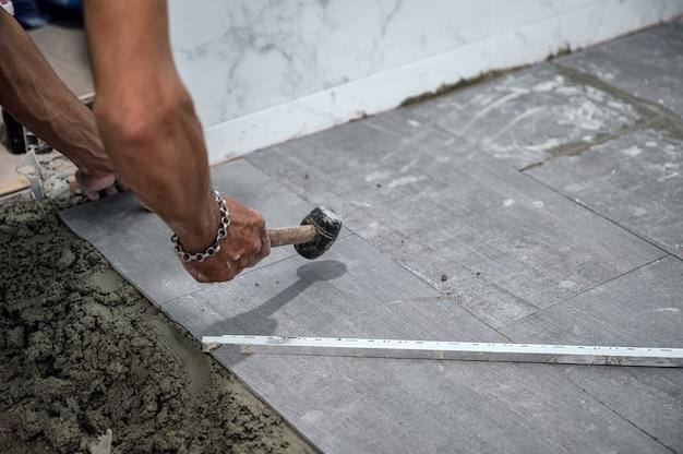 Ręka glazurnika układająca i używająca młotka pukającego płytki granitowe na podłodze