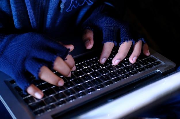 Ręka hakera kradnąca dane z laptopa od góry do dołu.