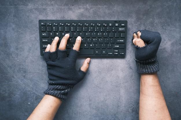 Ręka hakera kradnąca dane z laptopa