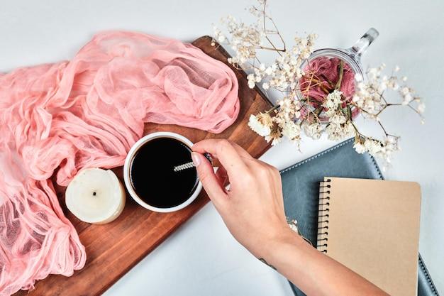 Ręka holdong filiżankę kawy na desce ze świecą, ponk szmatką i kwiatami.