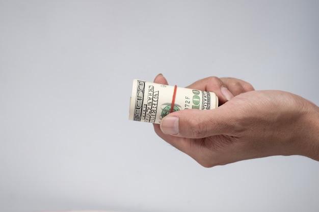Ręka holing banknotów dolarów amerykańskich na białym tle