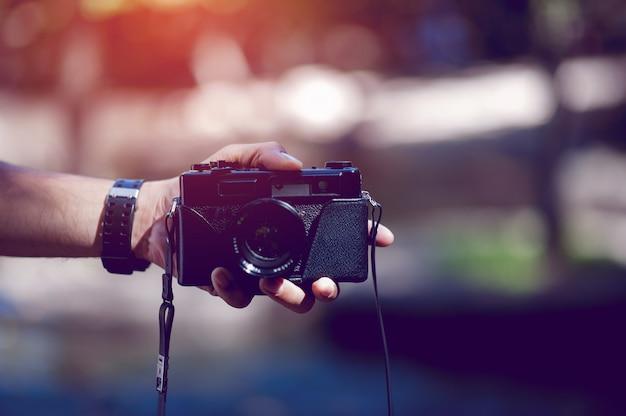 Ręka i aparat fotografa podróż w górach i fotograf przyrody concept