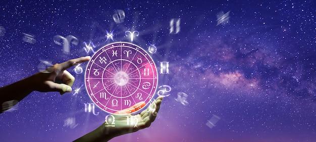 Ręka i astrologiczne znaki zodiaku wewnątrz okręgu horoskopu
