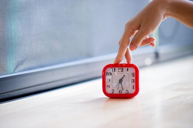 Ręka i czerwony budzik, który w ogóle pokazuje alarm każdego ranka koncepcja punktualności