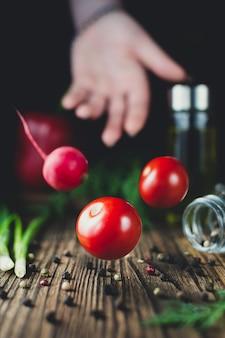 Ręka i lewitujące warzywa pomidory i rzodkiewki na drewnianym tle
