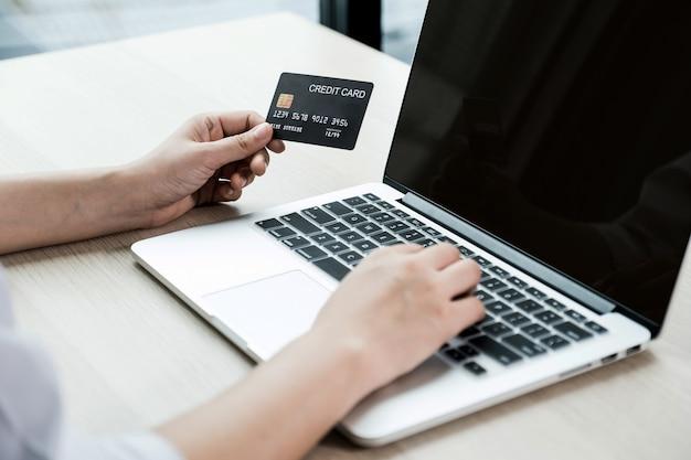 Ręka interesu trzymać kartę kredytową na zakupy online na komputerze przenośnym z domu, płatności e-commerce, bankowości internetowej, wydawanie pieniędzy.