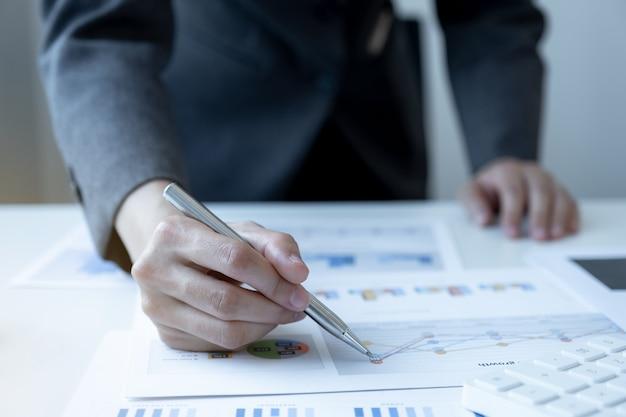 Ręka interesu trzymająca długopis i analizująca wykres w domowym biurze w celu ustalenia celu biznesowego