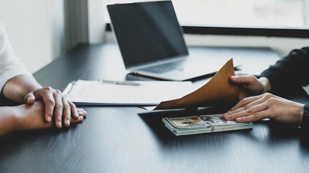 Ręka interesu trzymająca pieniądze z łapówki, aby urzędnicy podpisali kontrakty na projekty biznesowe, wkładali pieniądze do koperty, idee korupcji i przeciwdziałania łapówkarstwu.