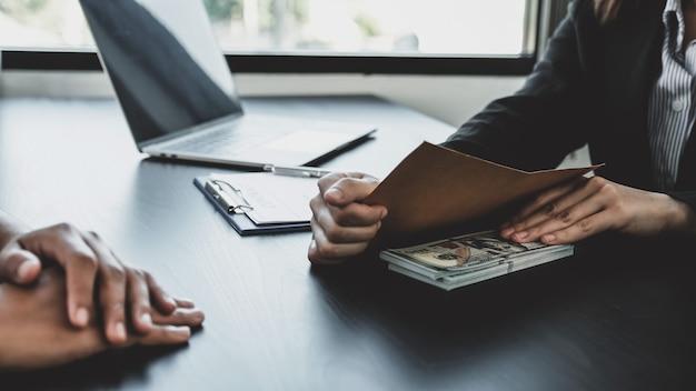Ręka interesu trzymająca pieniądze z łapówki dla urzędników państwowych podpisujących umowy na projekty biznesowe