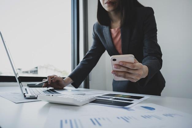 Ręka interesu trzymająca smartfon, analiza wykresu w domowym biurze w celu ustalenia celów biznesowych
