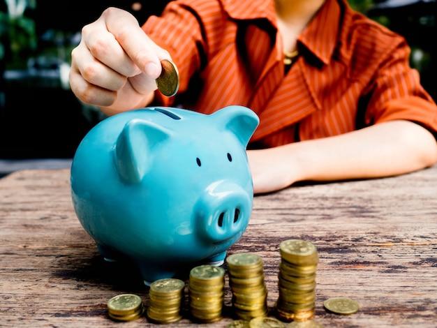 Ręka interesu wkładanie monety do niebieskiej skarbonki oszczędzanie pieniędzy na koncepcję funduszu emerytalnego