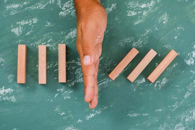 Ręka jako bariera dzieląca drewniane klocki.