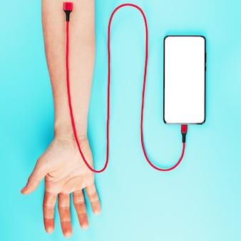 Ręka jest połączona czerwonym przewodem zasilającym ze smartfonem na niebieskiej powierzchni