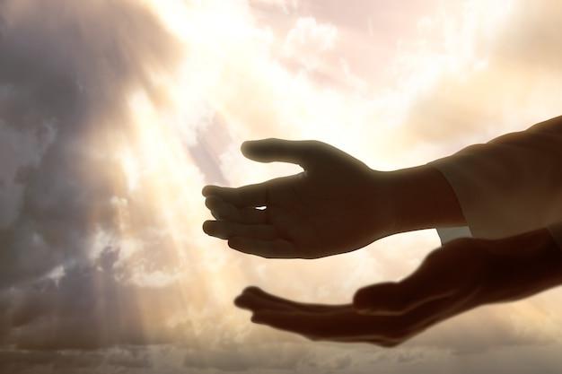 Ręka jezusa chrystusa modląca się do boga z dramatycznym niebem