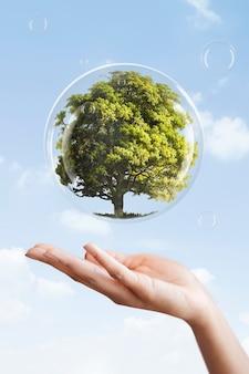 Ręka kampanii dnia ziemi pokazująca drzewo w bańce media mix