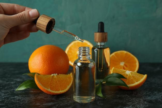 Ręka kapie olej w butelce na czarnym zadymionym stole