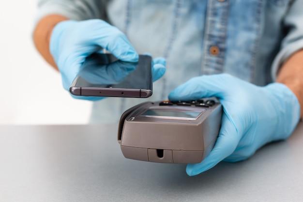 Ręka kasjera trzymająca czytnik kart kredytowych w jednorazowych rękawiczkach, płacąca smartfonem podczas pandemii covid-19.