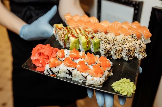 Ręka kelner trzyma zestaw pyszne świeże sushi łupek talerz, japońska surowa ryba w tradycyjnej restauracji. filadelfijskie świeże bułeczki serwowane na talerzu w sushi barze. kelner w rękawiczkach trzyma rolki sushi.