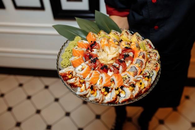 Ręka kelner trzyma zestaw pyszne świeże sushi łupek talerz, japońska surowa ryba w tradycyjnej restauracji.