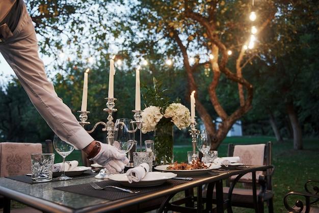 Ręka kelnera w rękawiczkach. pracownik jest zaangażowany w serwowanie stołu