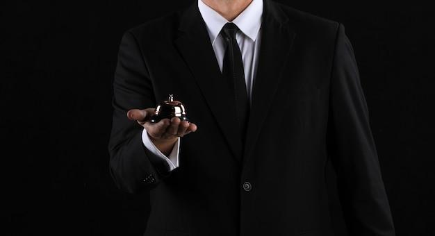 Ręka kelnera z wezwaniem obsługi na czarnym tle