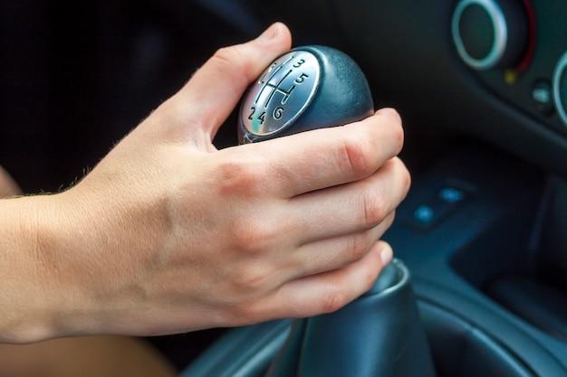 Ręka kierowcy ręcznie zmienia bieg. dziewczyna jedzie samochodem