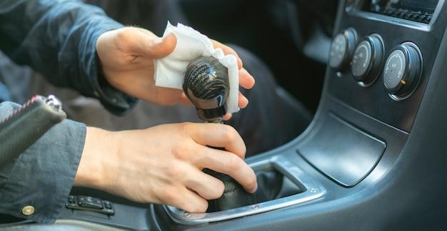 Ręka kierowcy trzymająca mikrofibrę i wycierająca wnętrze samochodu