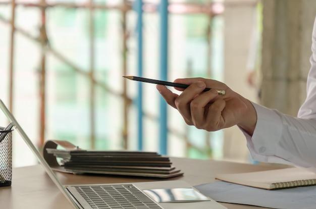 Ręka kierownika projektu wskazująca piórem na laptopie i plan na biurku podczas omawiania planowania nowego projektu na budowie, wykonawcy, koncepcji inżynieryjnej i budowlanej