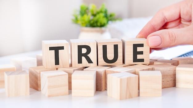 Ręka kładzie drewnianą kostkę z literą e od słowa true