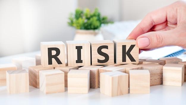 Ręka kładzie drewnianą kostkę z literą k ze słowa ryzyko. słowo napisane jest na drewnianych kostkach stojących na białej powierzchni stołu. komunikacja i koncepcje biznesowe