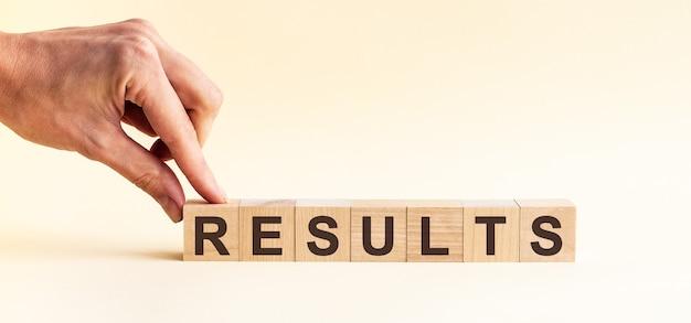 Ręka kładzie drewnianą kostkę z literą r ze słowa wyniki