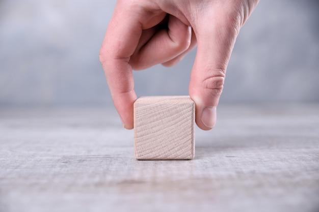 Ręka kładzie jeden pusty drewniany sześcian z miejscem na słowo, literę, symbol na stole. miejsce na tekst, wolne miejsce na kopię