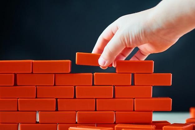Ręka kładzie ostatnią cegłę na ścianie. pojęcie budowy i budynku