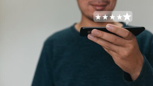 Ręka klienta trzyma smartphone i pięć gwiazdek z miejsca na kopię.