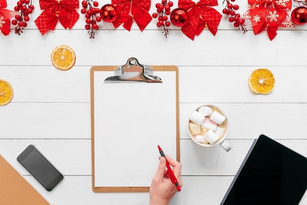Ręka kobieta pracuje przy biurowym stołem z boże narodzenie świątecznymi dekoracjami