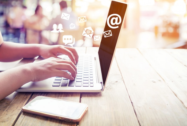 Ręka kobieta przy użyciu komputera przenośnego, wysyłanie wiadomości e-mail z symbolem adresu e-mail i ikona koperty. marketing online